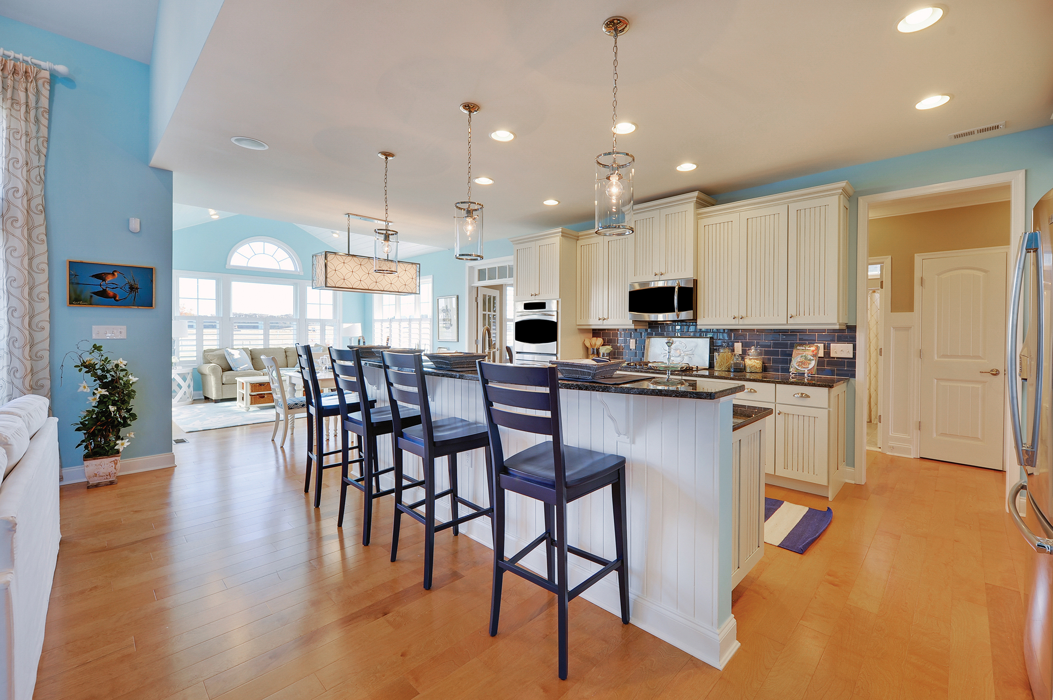 The combination of the bead board panel from the cabinets and wall paint color gives this casual kitchen a coastal feel. This casual design makes for a comfortable environment.