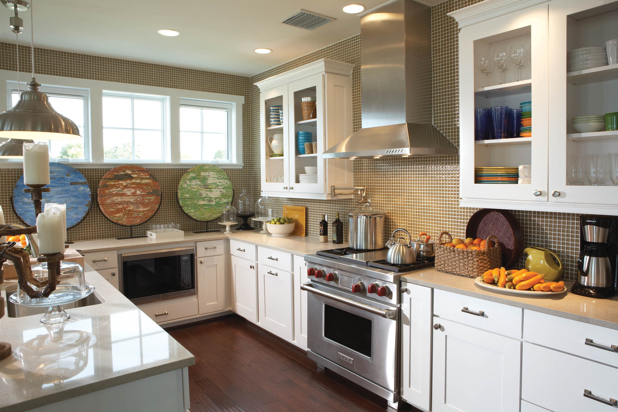 The simplistic cabinet doors and mix of design details blend to create a balanced transitional kitchen. Accessories such as the stainless light and candelabra add contemporary and traditional details to the kitchen.