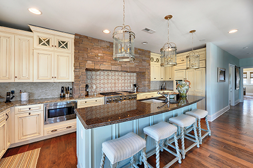 Light blue island cabinet in an off-white kitchen